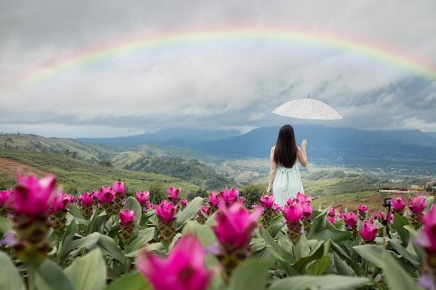 Alleinfrau, die regenschirm mit schönem regenbogen im blumengarten, hintere ansicht hält. Premium Fotos