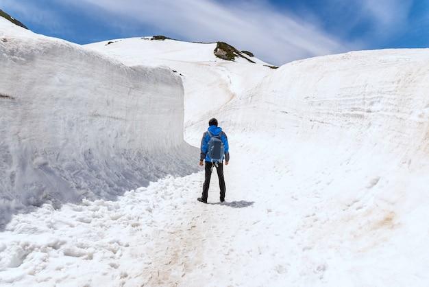 Alleinmann, der auf schneegehweg bei tateyama kurobe alpine route steht. Premium Fotos