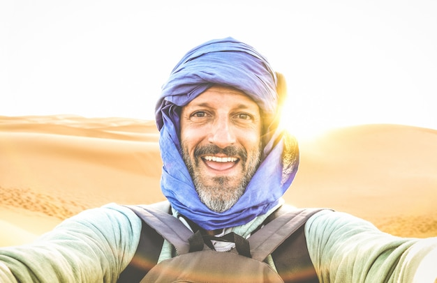 Alleinreisender des jungen mannes, der selfie an der wüstendüne erg chebbi nahe merzouga in marokko nimmt Premium Fotos