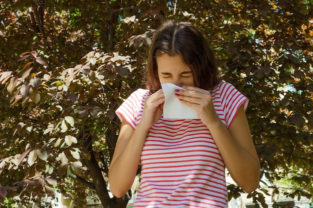 Allergie-konzept. niesendes junges mädchen mit nasenwischer unter blühenden bäumen im park Premium Fotos