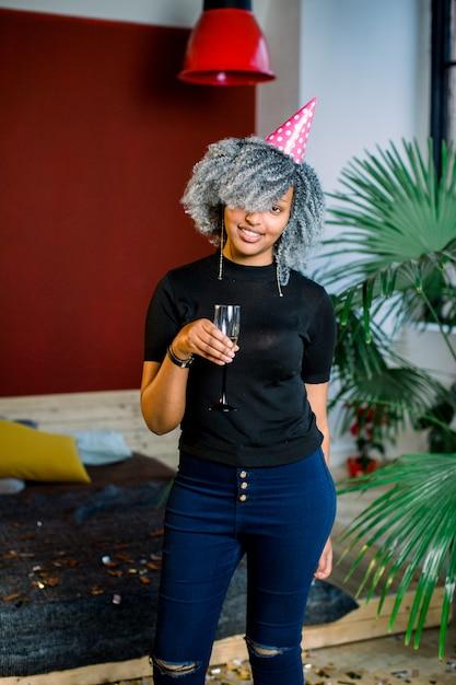 Alles gute zum geburtstag. mädchen mit konfetti und champagner auf der party. porträt der schönen lächelnden afrikanischen frau im geburtstagshut, der champagner in den händen hält, feiert feiertag. hohe auflösung. Premium Fotos