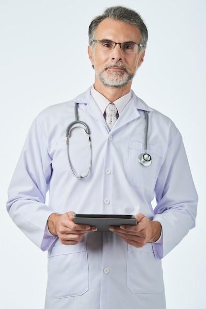 Allgemeinarzt mit stethoskop über den schultern, die den digitalen vorsprung halten und kamera betrachten Kostenlose Fotos