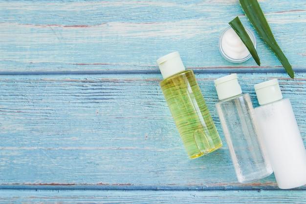 Aloe vera sprühflaschen und feuchtigkeitscremesahne auf blauem strukturiertem hölzernem hintergrund Kostenlose Fotos