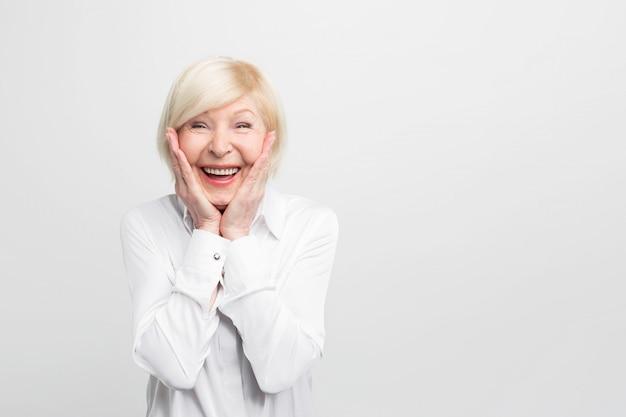 Alte, aber glückliche frau trägt weiße bluse und zeigt, dass sie sehr überrascht ist. sie hat viel glück. Premium Fotos