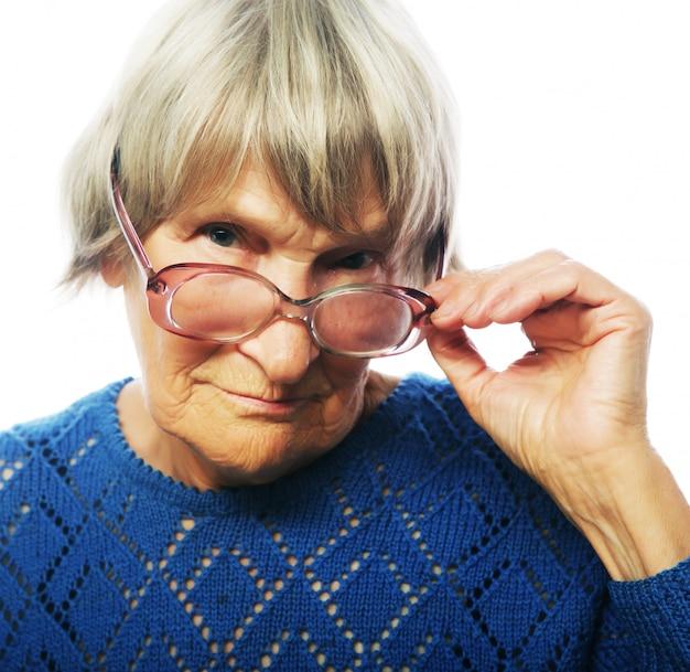 Alte ältere dame, die durch ihre brillen schaut Premium Fotos