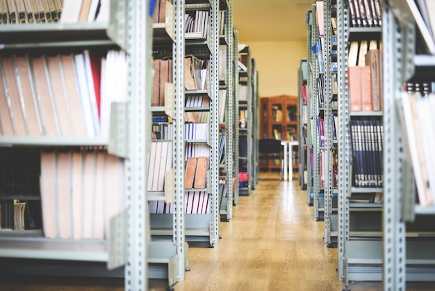 Alte bücher auf bücherregalhintergrund - bücherstapel im bibliotheksraum für geschäft und bildung Premium Fotos
