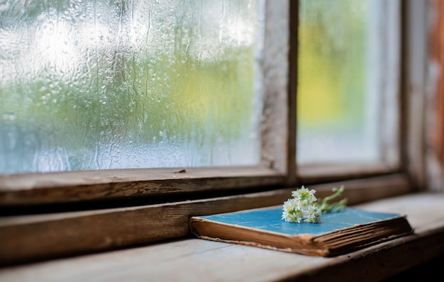 Alte bücher auf dem hintergrund des hölzernen nassen fensters des dorfs Premium Fotos