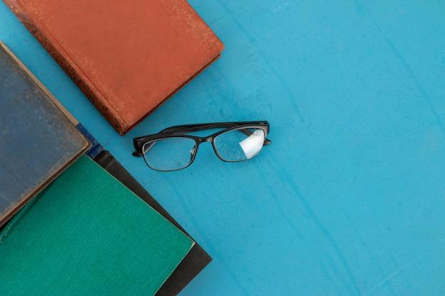 Alte bücher und schwarze gläser auf einem blaugrünen hölzernen. Premium Fotos