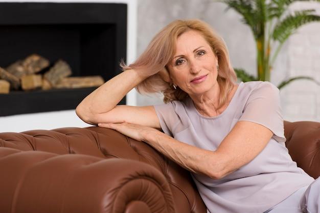 Alte dame, die auf sofa sitzt und kamera betrachtet Kostenlose Fotos
