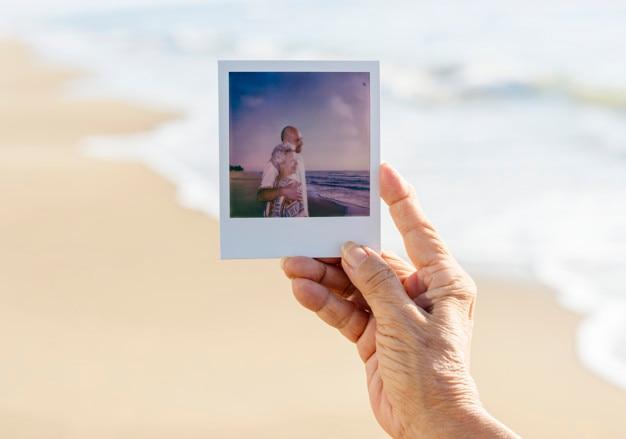 Alte dame, die ein foto am strand hält Kostenlose Fotos