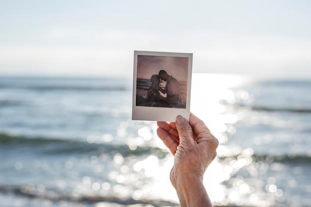 Alte dame, die eine fotografie am strand hält Premium Fotos