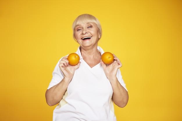 Alte dame in sportkleidung hat spaß mit orangen. Premium Fotos