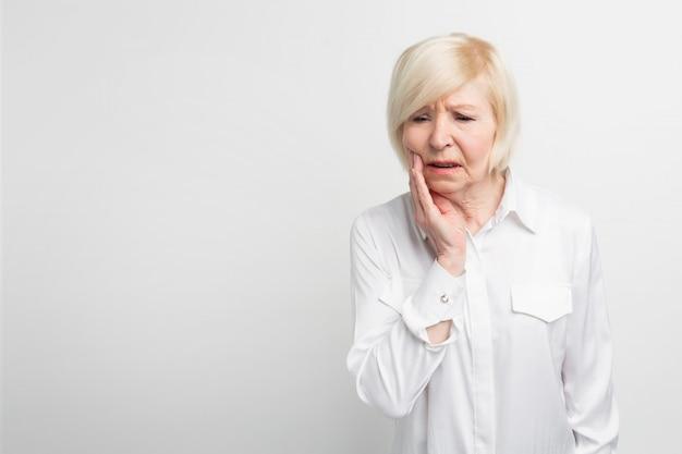 Alte dame leidet unter zahnschmerzen. es fing plötzlich an zu schmerzen. sie muss zum zahnarzt gehen. auf weißem hintergrund isoliert Premium Fotos