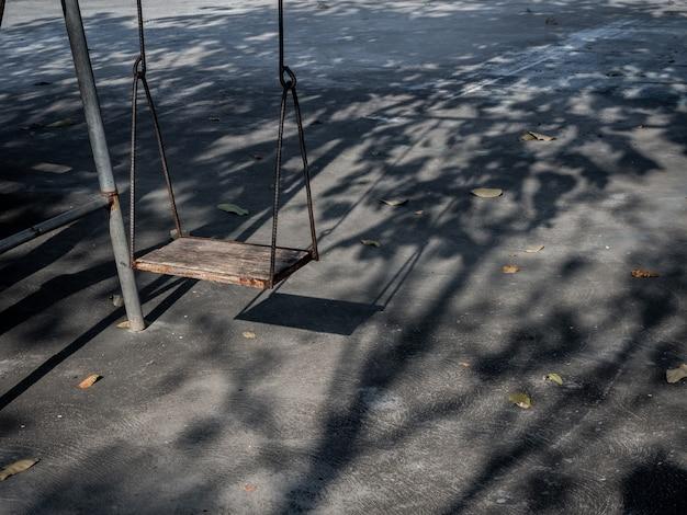 Alte einsame hölzerne schaukel auf sonnenuntergangszeit mit licht und schatten. Premium Fotos