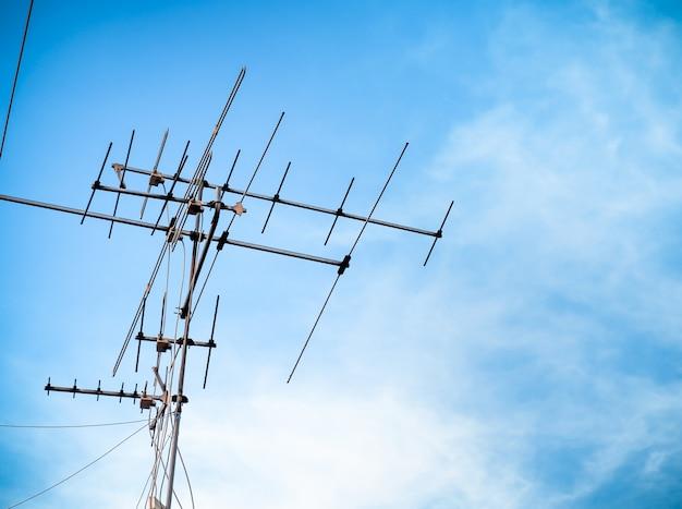 Alte fernsehantennensignalübertragung auf himmelblau. alte technologie fernsehkommunikation. Premium Fotos
