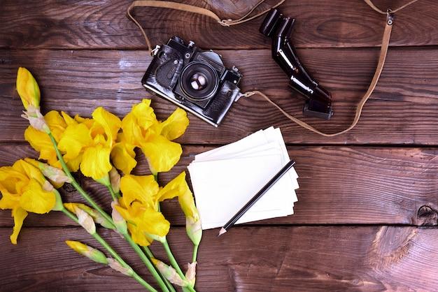 Alte filmkamera und ein strauß gelber iris Premium Fotos