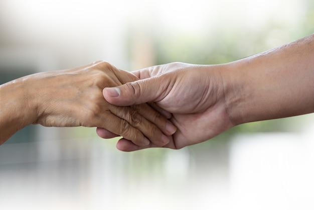 Alte frau und junge hand der leute, die das behinderte gehen mit unterstützung hält Premium Fotos
