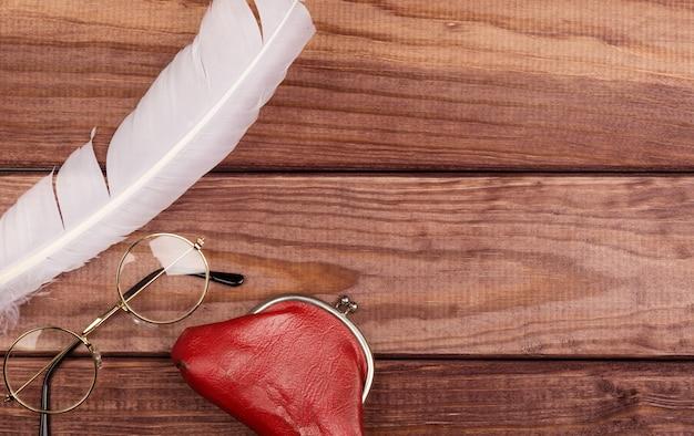 Alte gläser nähern sich feder- und weinlesegeldbeutel auf hölzernem hintergrund Premium Fotos