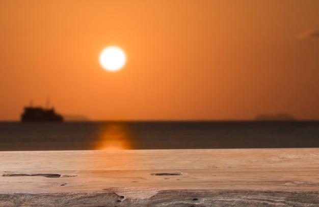 Alte holztischspitze mit seesonnenunterganghintergrund Premium Fotos