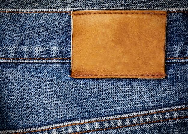 Alte jeansbeschaffenheit mit dem ledernen aufkleberhintergrundabschluß oben Premium Fotos
