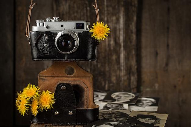 Alte kamera und gelber löwenzahn, weinlesestillleben Premium Fotos