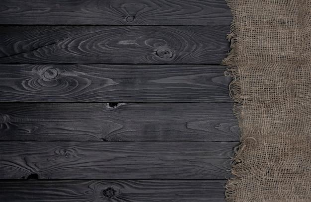 Alte leinwandgewebeserviette auf schwarzer hölzerner, draufsicht Premium Fotos