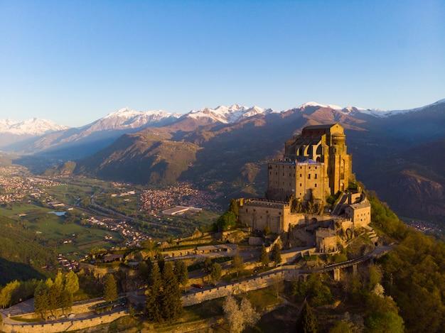 Alte mittelalterliche abtei der vogelperspektive hockte auf die gebirgsoberseite, schneebedeckte alpen des hintergrundes bei sonnenaufgang. sacra di san michele turin, italien Premium Fotos