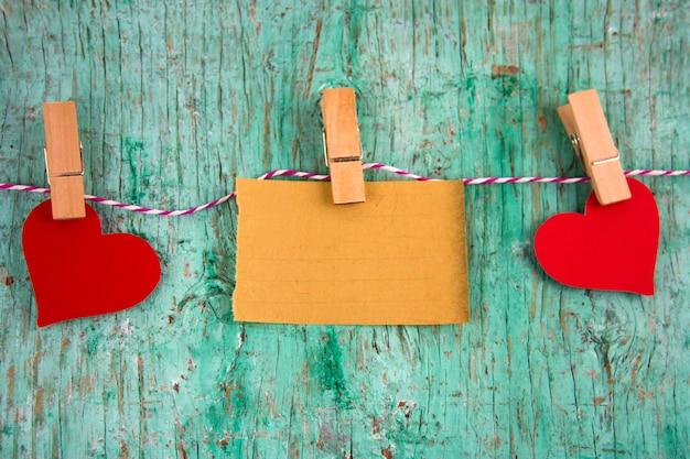 Alte rote herzen des leeren papiers und des papiers hingen an wäscheklammern an einem seil Premium Fotos