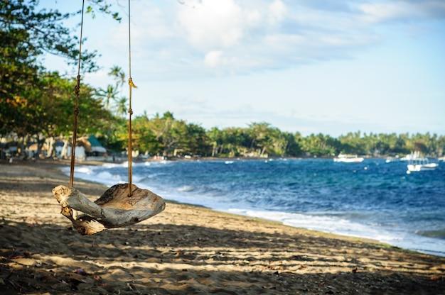 Alte schaukel am strand nahe dem meer in dumaguete, philippinen Kostenlose Fotos