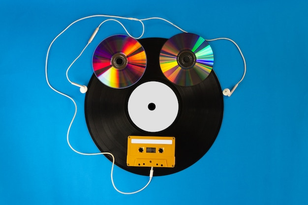 Alte vinylaufzeichnungen und cd mit audiokassettenband schaffen form ein roboter und ohr-kopfhörer auf blauem hintergrund Premium Fotos