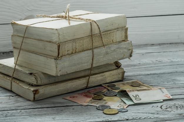 Alte weiße bücher mit geld und münzen auf holzwand Kostenlose Fotos