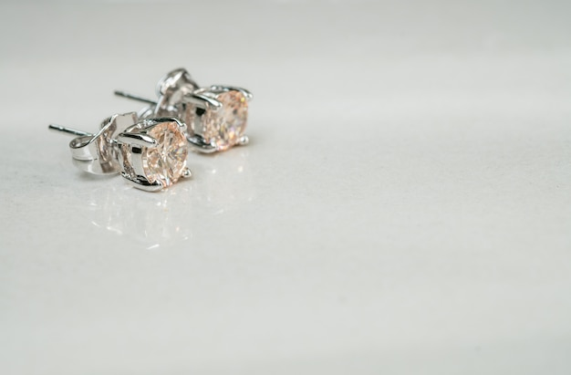 Alter diamantohrring der nahaufnahme auf unscharfem marmorbodenhintergrund Premium Fotos