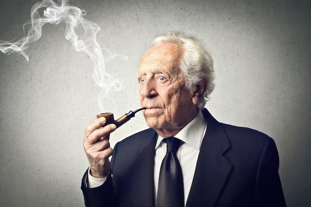 Alter eleganter mann, der eine pfeife raucht Premium Fotos