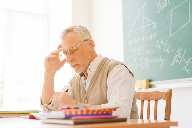 Alter lehrer, der hausarbeit im klassenzimmer überprüft Kostenlose Fotos