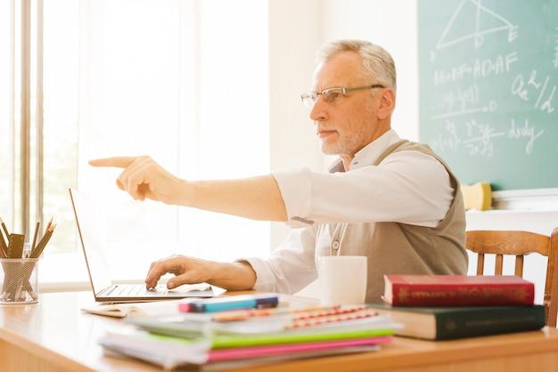 Alter lehrer, der in klassenzimmer zeigt Kostenlose Fotos