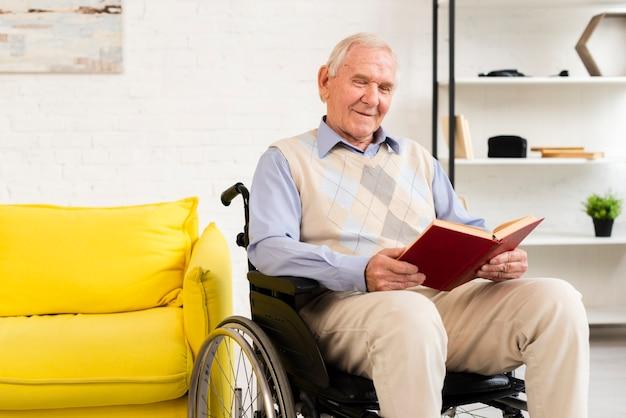 Alter mann, der auf rollstuhl beim lesebuch sitzt Kostenlose Fotos