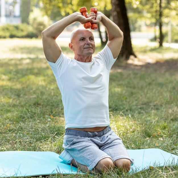 Alter mann, der auf yogamatte in der natur ausarbeitet Kostenlose Fotos