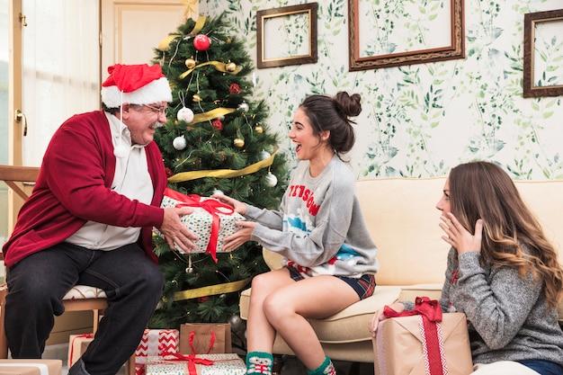 Alter mann, der der jungen frau große geschenkbox gibt Kostenlose Fotos