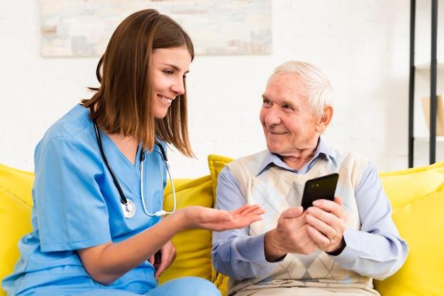 Alter mann, der der pflegekraft fotos am telefon zeigt Kostenlose Fotos