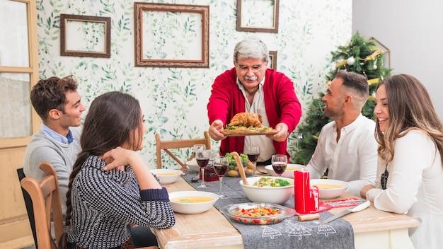 Alter mann, der gebackenes huhn auf festliche tabelle setzt Kostenlose Fotos