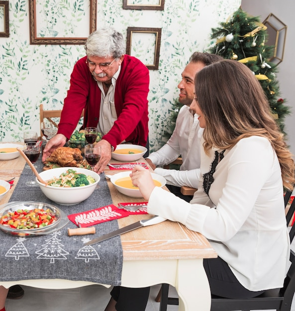 Alter mann, der gebratenes huhn auf weihnachtstabelle setzt Kostenlose Fotos