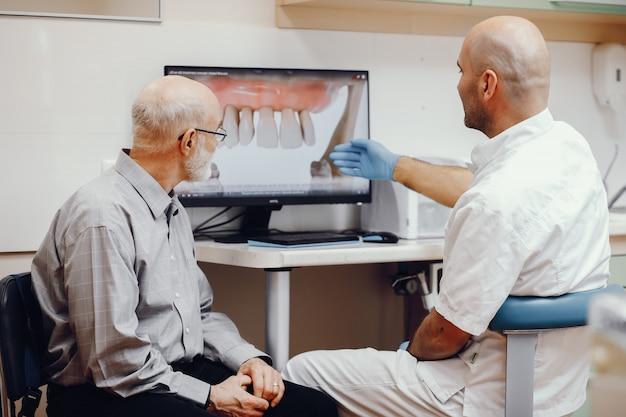 Alter mann, der im büro des zahnarztes sitzt Kostenlose Fotos