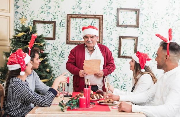 Alter mann, der mit papier am festlichen tisch steht Kostenlose Fotos