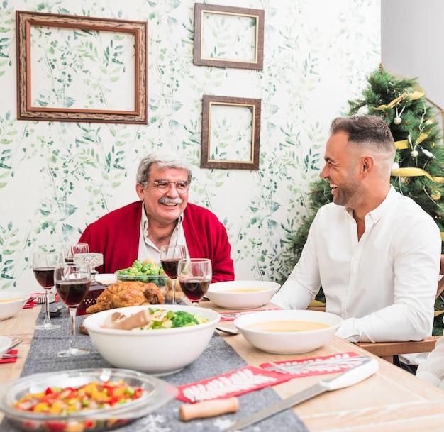 Alter mann, der mit sohn am festlichen tisch spricht Kostenlose Fotos