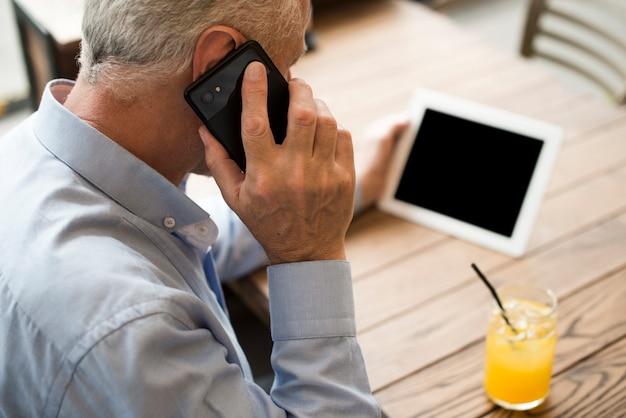 Alter mann der nahaufnahme, der am telefon spricht Kostenlose Fotos