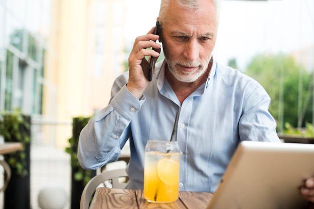 Alter mann der vorderansicht, der am telefon spricht Kostenlose Fotos