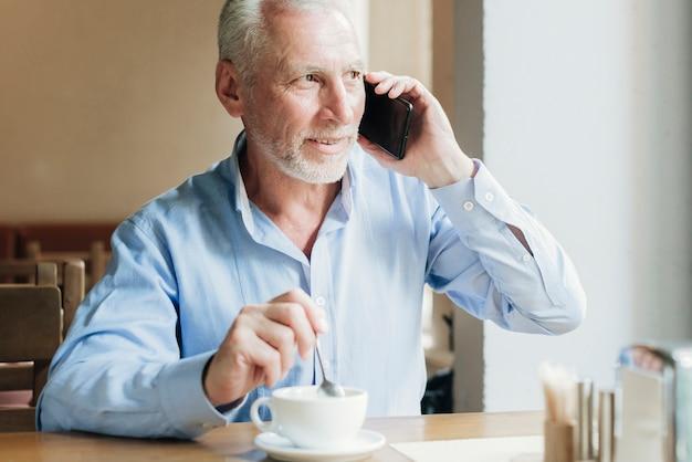 Alter mann des mittleren schusses, der am telefon spricht Kostenlose Fotos