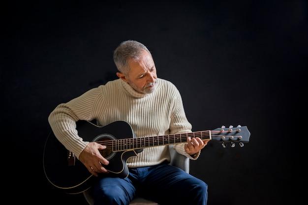 Alter mann des mittleren schusses, der gitarre spielt Kostenlose Fotos