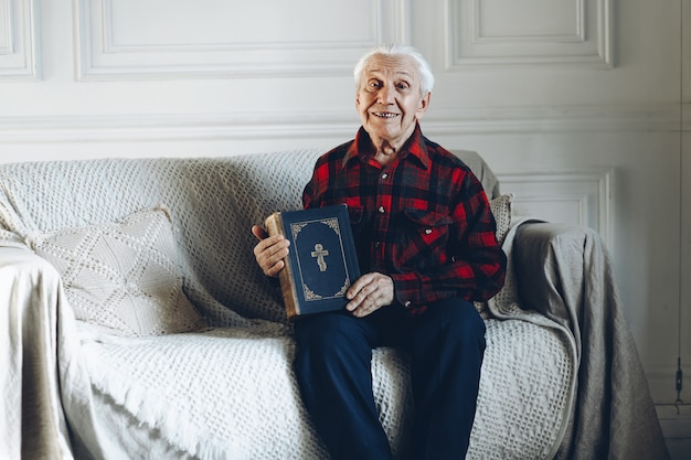 Alter mann hält ein buch Premium Fotos