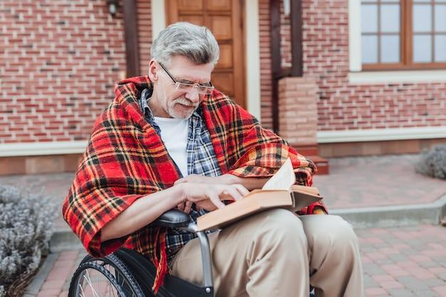 Alter mann im rollstuhl lesen interessante roman und posiert in die kamera in der nähe von pflegeheim Premium Fotos